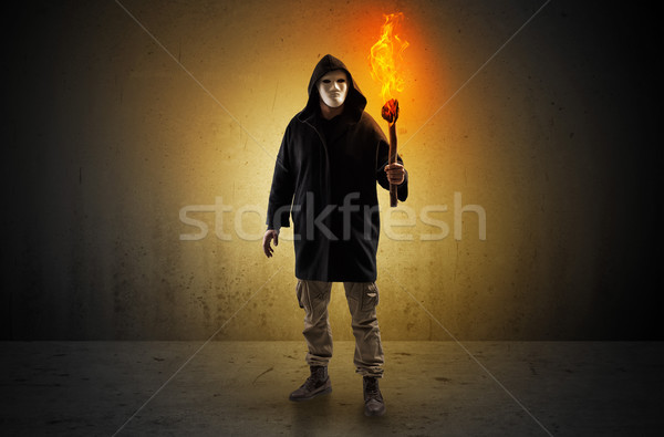 Man walking in an empty space with burning flambeau Stock photo © ra2studio