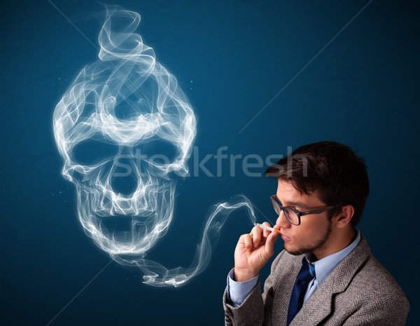 Młody człowiek palenia niebezpieczny papierosów toksyczny czaszki Zdjęcia stock © ra2studio