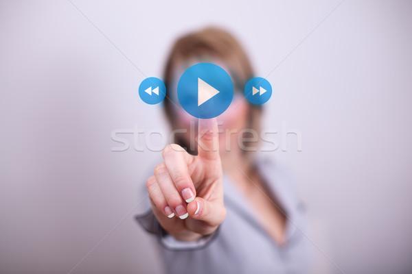 Woman pressing play media button Stock photo © ra2studio