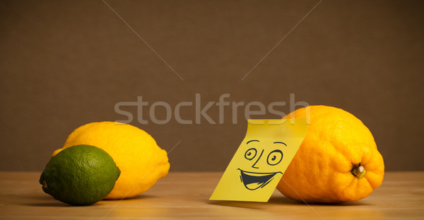Lemon with post-it note smiling at citrus fruits Stock photo © ra2studio