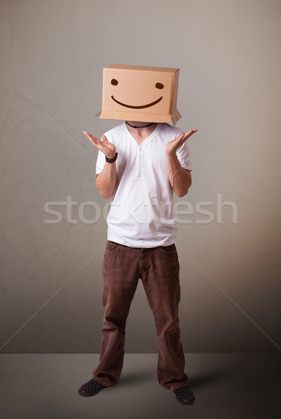 Young man gesturing with a cardboard box on his head with smiley Stock photo © ra2studio