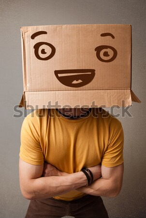 Young man gesturing with a cardboard box on his head with evil f Stock photo © ra2studio