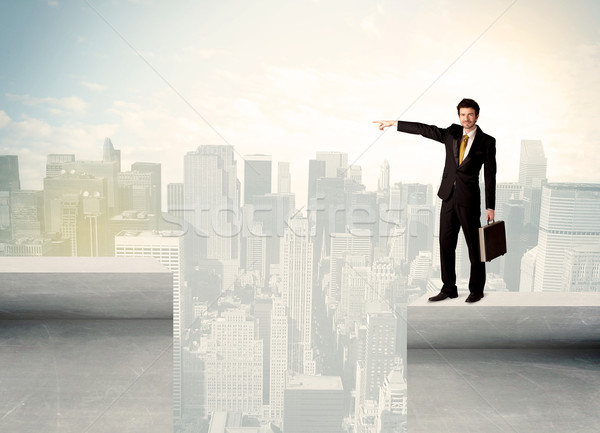Businessman standing on the edge of rooftop Stock photo © ra2studio