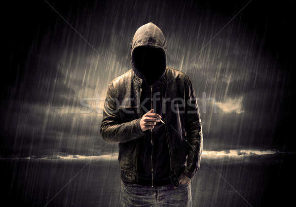 Stock photo: Anonymous terrorist in hoodie at night