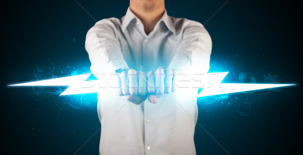 Business man holding glowing lightning bolt in his hands Stock photo © ra2studio
