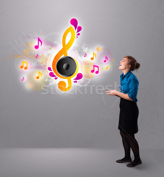 pretty girl singing and listening to music with musical notes Stock photo © ra2studio