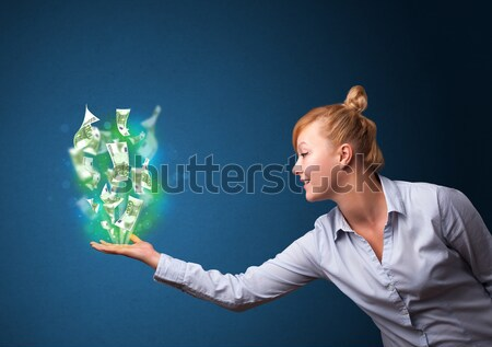 Glowing money in the hand of a businesswoman Stock photo © ra2studio