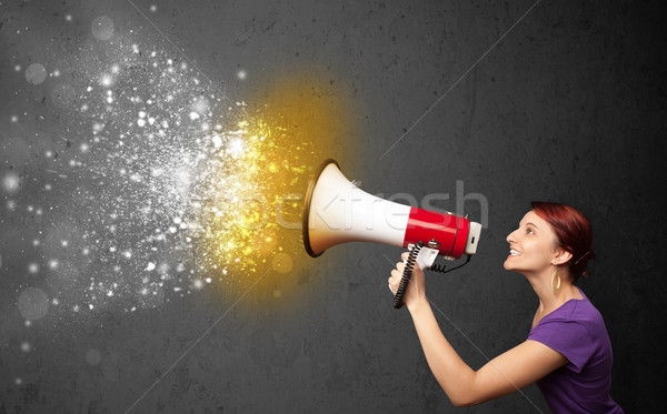 Woman shouting into megaphone and glowing energy particles explode concept Stock photo © ra2studio