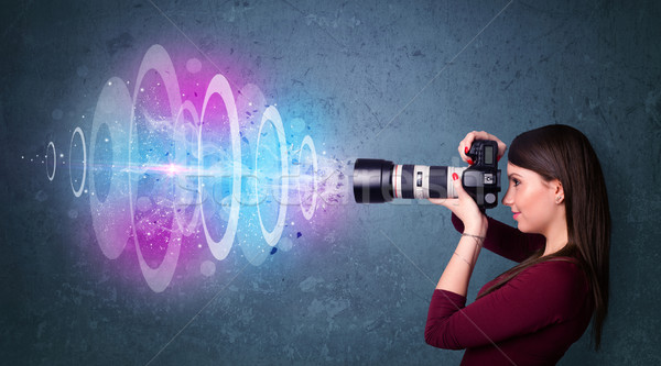 Photographer girl making photos with powerful light beam Stock photo © ra2studio