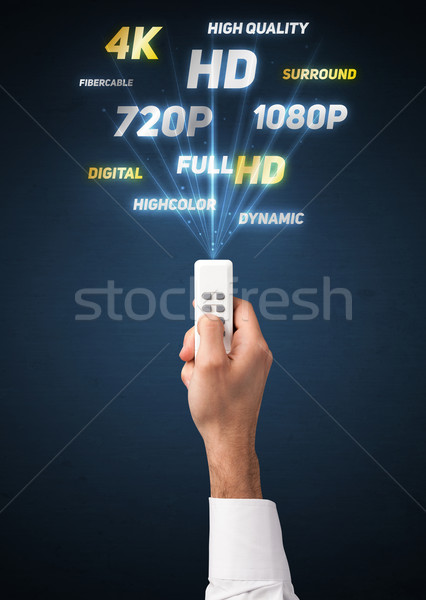 Hand with remote control and multimedia properties Stock photo © ra2studio