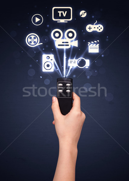 Hand with remote control and media icons Stock photo © ra2studio