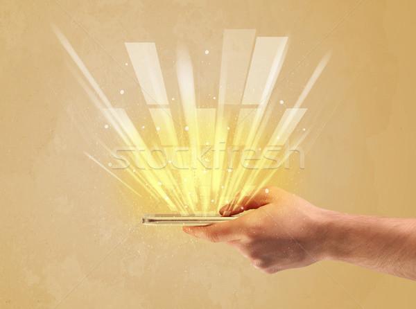 Hand with telephone and yellow light Stock photo © ra2studio
