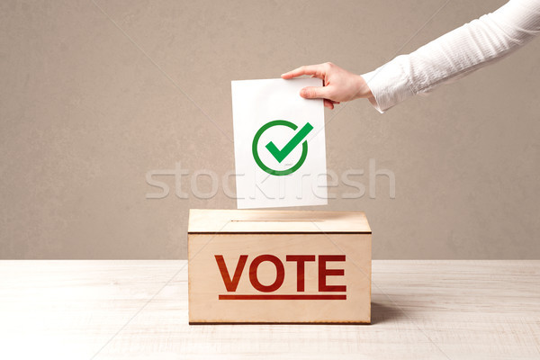 Close up of male hand putting vote into a ballot box Stock photo © ra2studio
