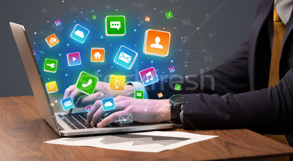 Hand using laptop with application icons flying around Stock photo © ra2studio