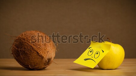 Apple with sticky post-it note looks sadly at coconut Stock photo © ra2studio