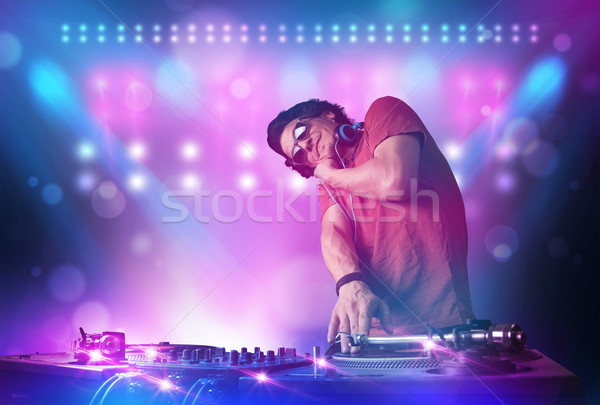 Disc jockey mixing music on turntables on stage with lights and  Stock photo © ra2studio