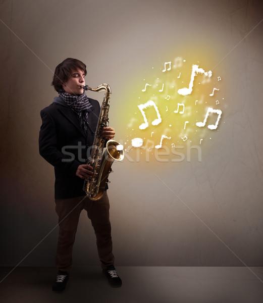 Przystojny muzyk gry saksofon muzyki zauważa młodych Zdjęcia stock © ra2studio