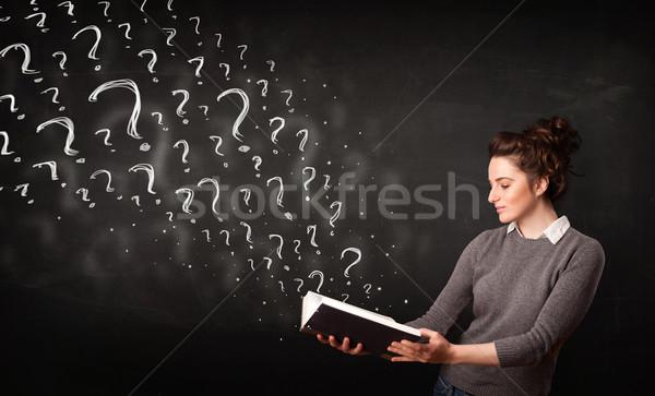 Foto stock: Mulher · bonita · leitura · livro · pontos · de · interrogação · fora · confuso