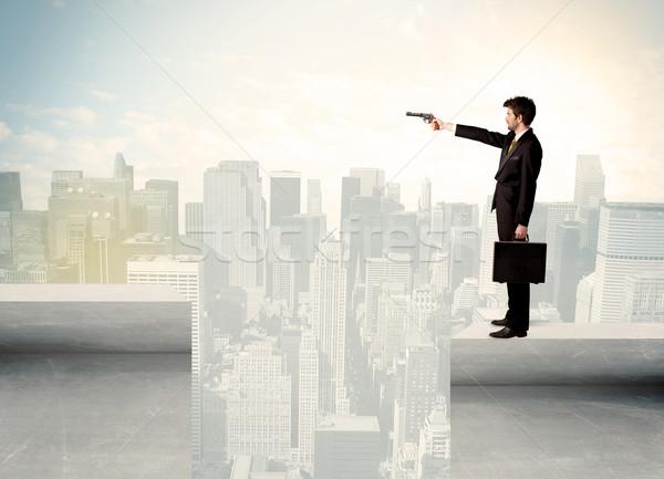 Businessman standing on the edge of rooftop Stock photo © ra2studio