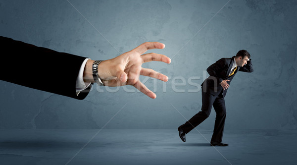 Business man running away from a huge hand concept Stock photo © ra2studio