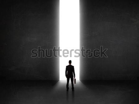 Uomo d'affari guardando muro luce tunnel apertura Foto d'archivio © ra2studio