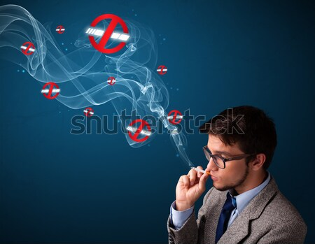 Attractive young man smoking dangerous cigarette with no smoking signs Stock photo © ra2studio