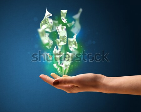 Glowing money in the hand of a woman Stock photo © ra2studio