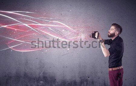 Man with airbrush spray paint with car, boat and motorcycle drawing on dark background Stock photo © ra2studio