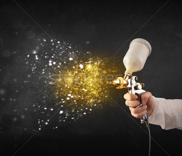 Worker with airbrush painting with glowing golden paint  Stock photo © ra2studio