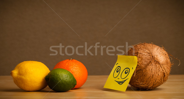 Coconut with post-it note looking at citrus fruits Stock photo © ra2studio