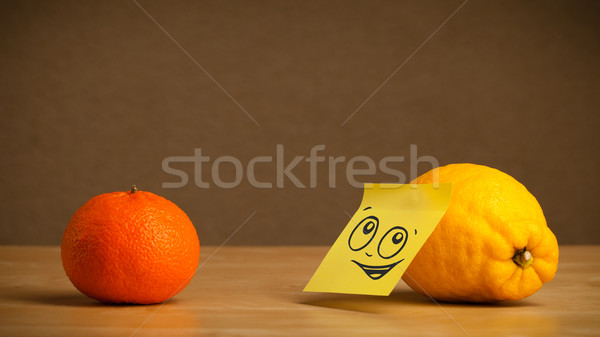 Stock photo: Lemon with post-it note looking at orange