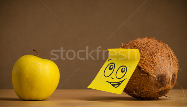Coconut with post-it note looking at apple Stock photo © ra2studio