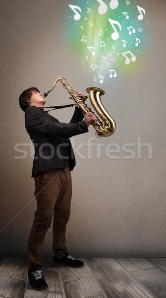 Jóvenes músico jugando saxófono notas musicales atractivo Foto stock © ra2studio