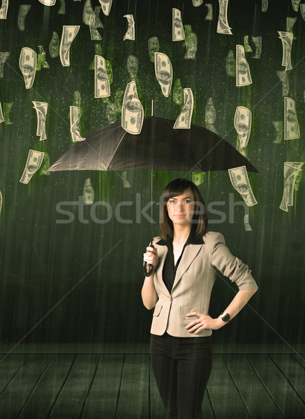 Stock photo: Businesswoman standing with umbrella in dollar bill rain concept