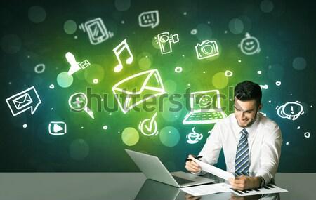 üzletember közösségi média szimbólumok ül fekete asztal Stock fotó © ra2studio