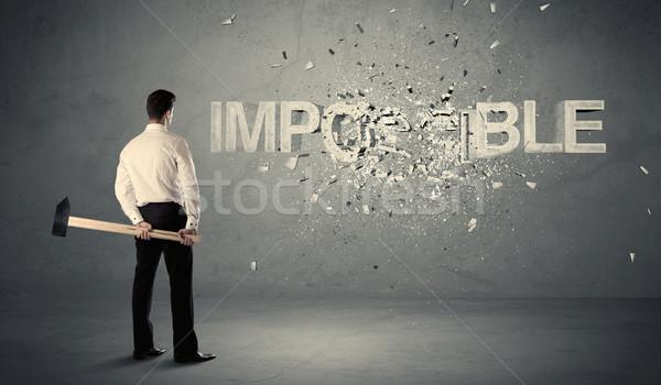 Homme d'affaires impossible signe marteau mur Photo stock © ra2studio