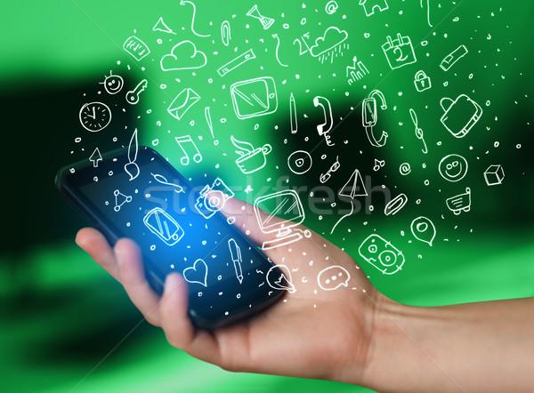 Hand holding smartphone with hand drawn media icons and symbols Stock photo © ra2studio