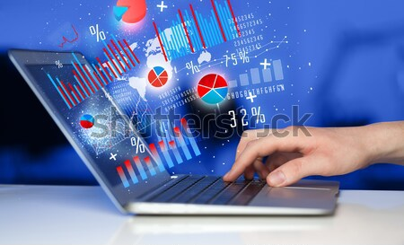Hand typing on modern laptop notebook computer with graph icons  Stock photo © ra2studio