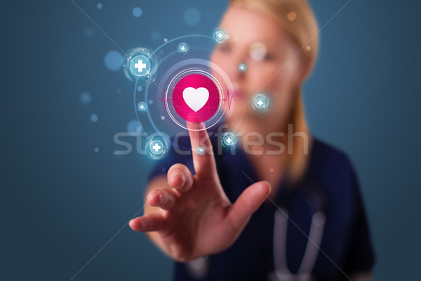 Young nurse pressing modern medical type of buttons Stock photo © ra2studio