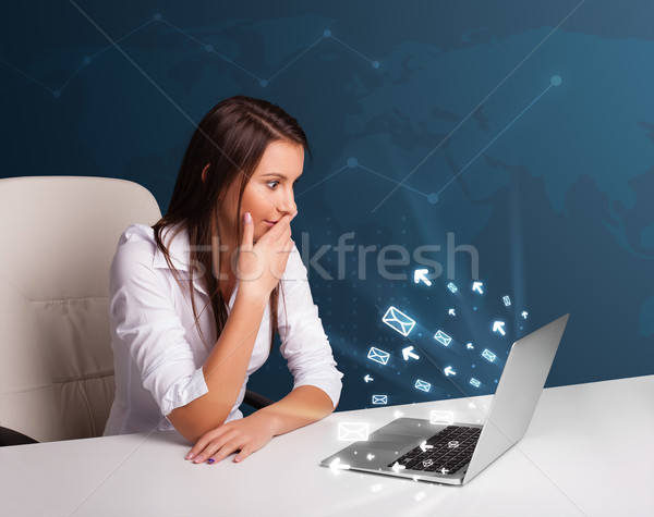 Young lady sitting at dest and typing on laptop with message ico Stock photo © ra2studio