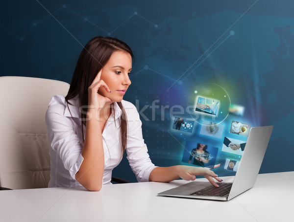 Beautiful girl sitting at desk and watching her photo gallery on Stock photo © ra2studio