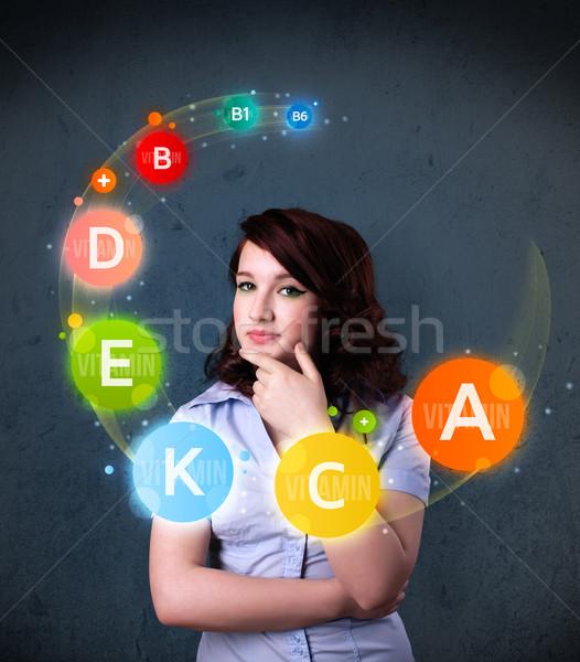 Young woman thinking with vitamins circulation around her head Stock photo © ra2studio