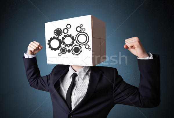 Businessman gesturing with a cardboard box on his head with spur Stock photo © ra2studio