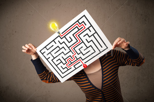 Woman holding a paper with a labyrinth on it in front of her hea Stock photo © ra2studio