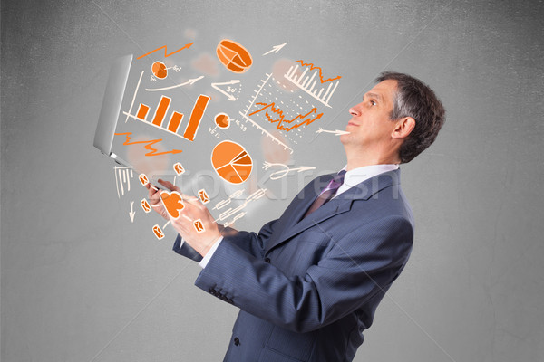 Imprenditore notebook grafici statistiche suit Foto d'archivio © ra2studio
