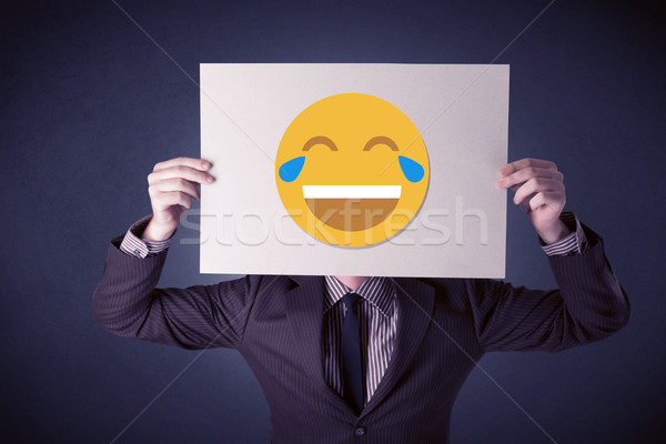 Businessman holding paper with laughing emoticon Stock photo © ra2studio