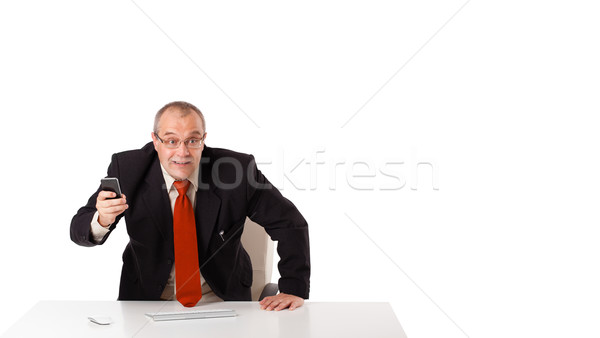 businessman sitting at desk and holding a mobilephone with copys pace, isolated on white Stock photo © ra2studio