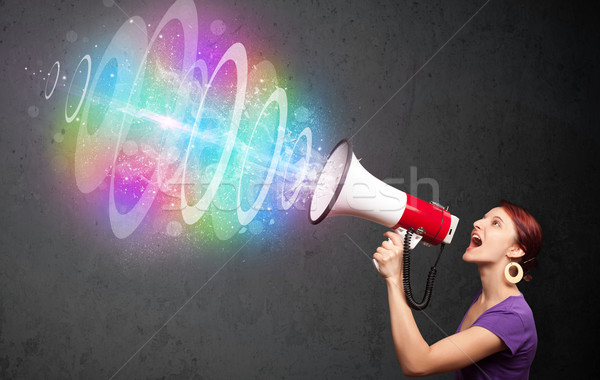 Cute young girl yells into a loudspeaker and colorful energy beam comes out Stock photo © ra2studio