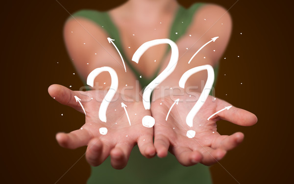 Young woman presenting hand drawn question marks Stock photo © ra2studio