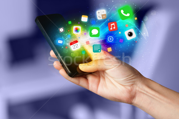 Hand holding smartphone with colorful app icons Stock photo © ra2studio